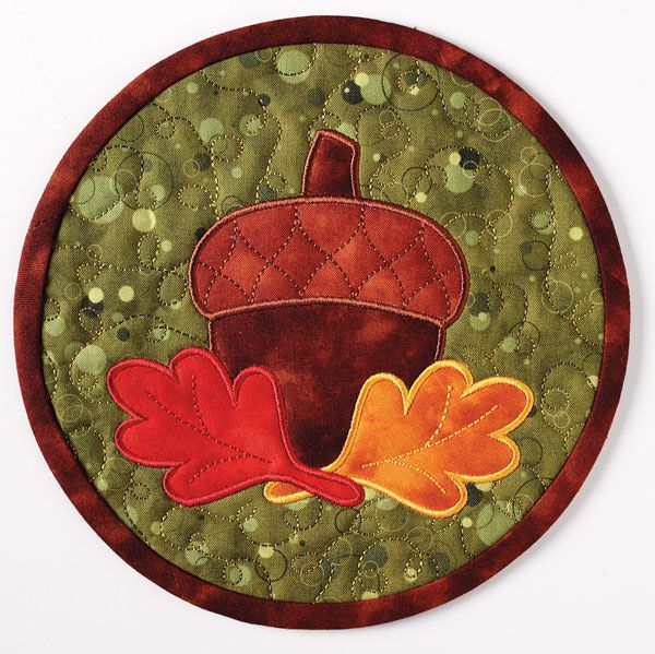 This mini mat features an appliqué acorn and leaf design on a green background and swirls of quilting. This mini mat can be used as a mug mat, hot pad or trivet. Digital pattern and kit available!