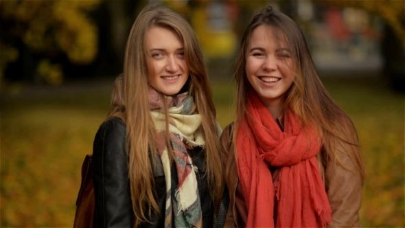 Two Smiling Young Attractive Girls with Autumn Leaves in Park at Fall Outdoors, Girlfriends Smiling