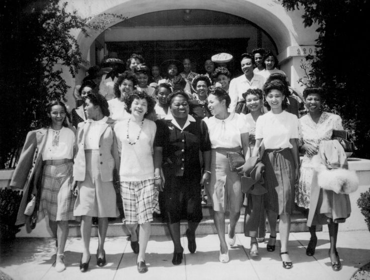 """Hattie McDaniel (center), Chairman of the Negro Division of the Hollywood Victory Committee, takes time off from rehearsals...to lead a caravan of entertainers and hostesses to Minter Field,...for a vaudeville performance and dance for soldiers stationed there. The young lady to the right of Miss McDaniel is Miss Virginia Paris, noted concert singer."""