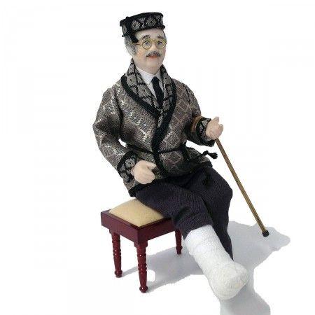 """Älterer Herr mit Gipsbein (46075). Feine hangefertigte Porzellan-Gliederpuppen beleben jede Szene. Die Bekleidung wurde aus exquisiten Stoffen mit besonders feinen Mustern handgeschneidert und den einzelnen Figuren """"auf den Körper maßgeschneidert"""". Arme, Beine und Körper lassen sich in jede beliebige Stellung bringen, der Kopf läßt sich drehen. Unser Sitzhocker (95060) gehört nicht zum Lieferumfang."""