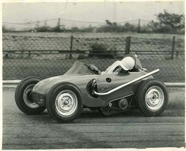 Atom racing car at the Wimbledon Speedway in 1955: 'Midget Racer undergoes trials. Essex: Wimbledon Speedway rider Cyril Brine leans out to see how high the front wheel will lift on a bend during trials of the Atom Car - claimed to be the smallest racing car in the world. No brakes are fitted and the only controls are clutch and throttle.'