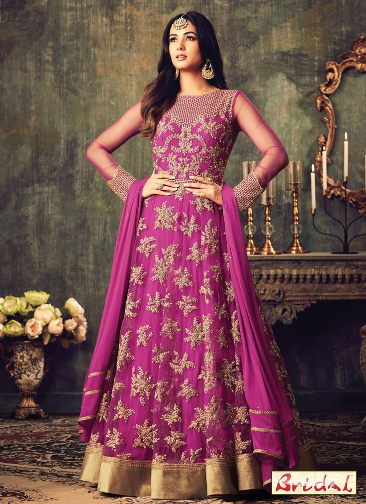 Add richer looks to a persona with this magenta net floor length anarkali suit. This pretty dress is showing some fantastic embroidery done with embroidered, patch border and resham work. Comes with m...