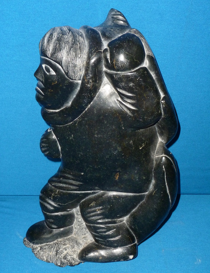 """Item # C6276 Price: C$3,975 Subject: The Big Catch Dated: 1975 - Signed Artist: Link   Nastapoka, Samson      Community:  Link   Inukjuak       Size: inches/cm 17.5"""" x 11"""" x 6.5"""" 44.5 cm x 27.9 cm x 16.5 cm   Description: This substantial sculpture depicts a supremely successful Inuit hunter returning with his catch of two, huge fish. The weight and curves of the fish mould and balance the man's body as he hauls the catch."""