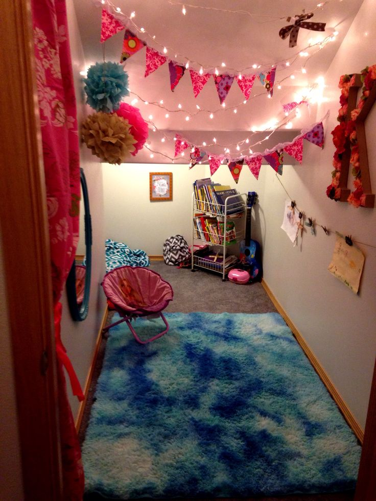 Under the stairs playroom for a little girl. Features and over dyed shag rug and tissue paper Pom Poms. It has lots of storage and it's perfect for a party or sleepover anytime!