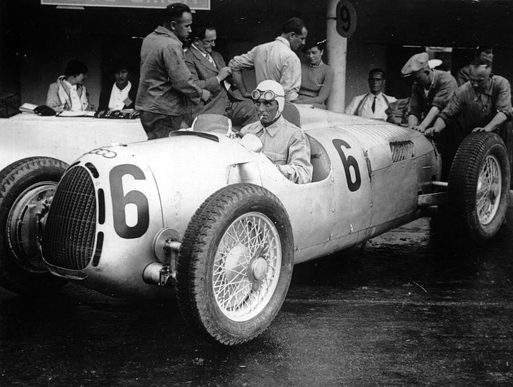 Racing driver Achille Varzi has a cigarette during a pit stop for his Auto Union car. The Auto Union was one of the first rear engine Formula 1 racing cars.