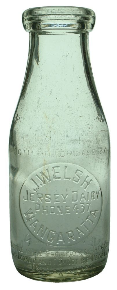 Embossing: This bottle contains / Milk / Bottled for sale by / J. Welsh / Jersey Dairy / Phone 437 / Wangaratta / Bottle is the property of the above / it is loaned and cannot be legally / used by others // One Imperial Pint. Base: 619 / small impressed 052. (Victoria) Type: Household Dairy /  Era: 1950s /  Variety: Wide mouth or wad top. Seam through lip. Clear. Pint. /  Height: 205 mm /  Condition: Good. Has a 10 x 9 mm chip to the back left lip. A few other little fleabites around. Crate…