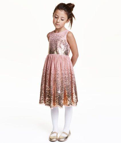 Rosa/Guld. En klänning i paljettbeströdd tyll. Klänningen har dolda tryckknappar bak. Avskuren i midjan med utställd, tyllfodrad kjol. Helfodrad i vävd strl 104