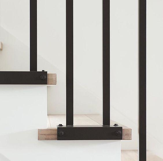 Dark metal balusters, white stringers and pale oak stair treads.