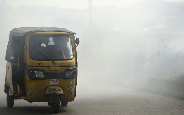 Strange black soot causes anxiety in Port Harcourt   A rick shaw carries passengers through smoke emitted from a dump in the city of Port Harcourt Rivers State on February 14 2017.<br />The Nigerian city of Port Harcourt used to be known as The Garden City since late last year black soot has been falling from the sky scaring and angering residents who claim nothing is being done to protect their health. / AFP PHOTO / PIUS UTOMI EKPEI The Nigerian city of Port Harcourt used to be known as The…