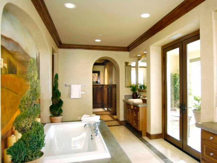 French doors open to a luxurious, Mediterranean style bathroom with a large, white bathtub and indoor topiary plants. His and hers vanities flank the doors.