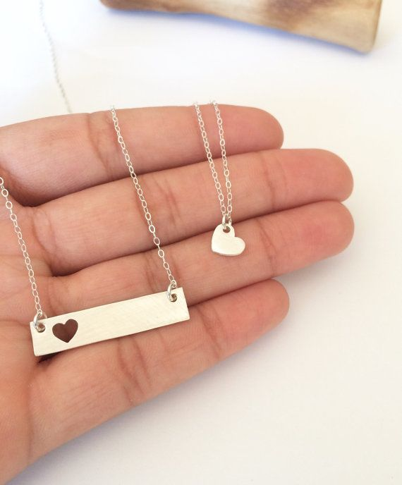 A beautiful mother daughter necklace set, featuring a heart silhouette bar necklace and a tiny heart necklace.  Both necklaces are made with