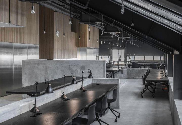 Un'estetica razionale e pulita per l'ambiente di lavoro open space di Flamingo Shanghai Office, costituito da un'infilata di scrivanie in rovere scuro, ciascuna dotata di lampada da tavolo nera. Stesso colore per le poltroncine ergonomiche su ruote