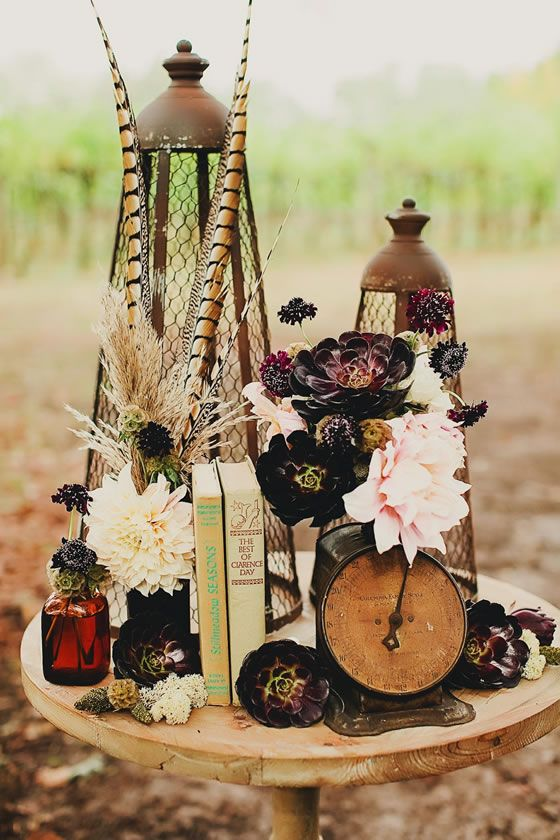 A wedding centerpiece with vintage books, an antique clock, stunning peonies and succulents.