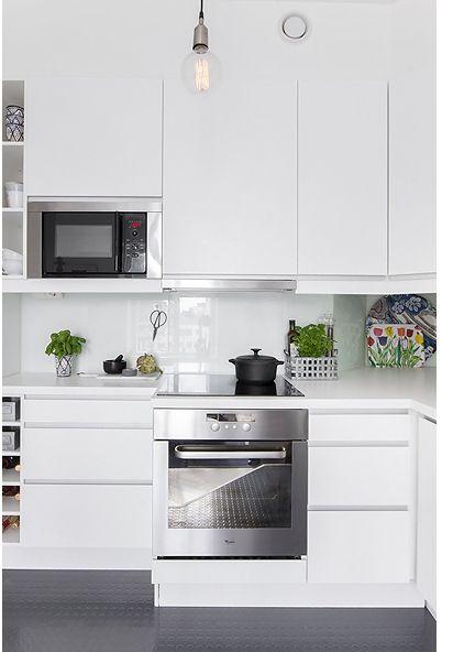 Les petites surfaces du jour : un deux pièces entièrement blanc. Cocina con microondas en un gabinete abierto junto a los estantes abiertos.