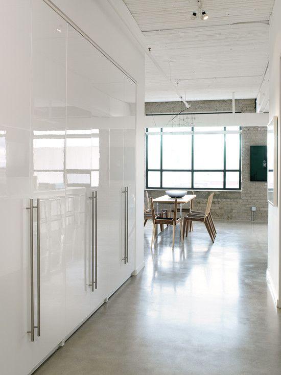 opción para el garaje, gabinetes blancos, piso de cemento pulido, una pared en piedra o ladrillo
