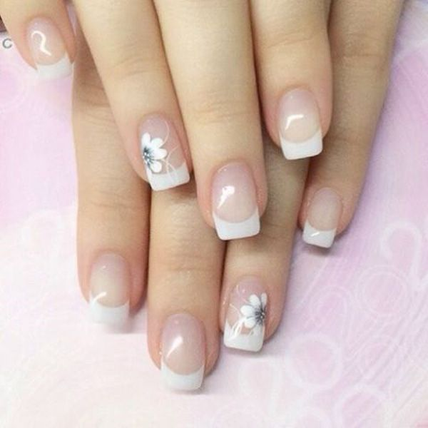 Pretty white French tips in flora design. Add a beautiful flower design on top of your French tips to give that glowing and elegant feel to the design.