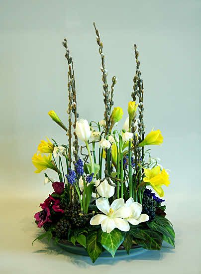 This arrangement has been made in a green glazed round pottery plant pot saucer.