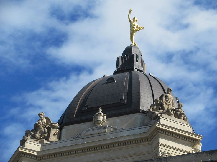 The Golden Boy atop the Legislative Building in Winnipeg, Manitoba, Canada, carries a torch in his right hand and a sheaf of wheat in his left.