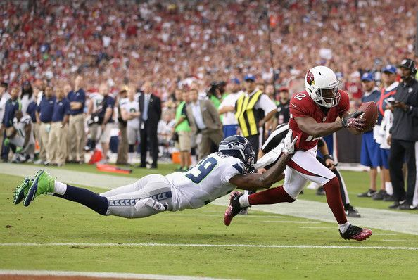 Wide receiver Andre Roberts #12 of the Arizona Cardinals reaches the football into the endzone to score a 6 yard touchdown reception past cornerback Brandon Browner #39 of the Seattle Seahawks during the fourth quarter of the season opener at the University of Phoenix Stadium on September 9, 2012 in Glendale, Arizona.