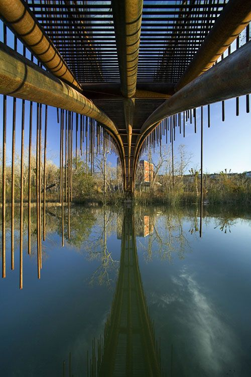 """To connect a house to a guest house of their design in Austin, Texas, Miró Rivera Architects designed a pedestrian footbridge that takes its cues from its natural context. The bridge uses 5"""" diameter pipes for its 80' span, with 1/2"""" diameter bars acting as decking and guardrails. The bars are bent up and down, each ending at irregular heights."""
