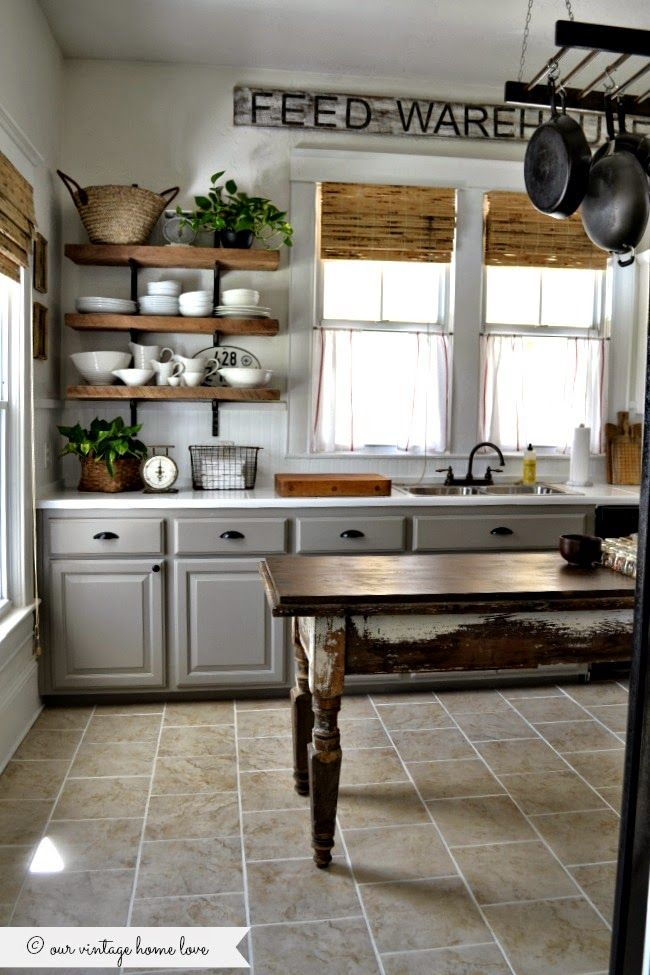 Painted greige / taupe lower cabinets, painted tile countertops, rustic wood plank open shelving