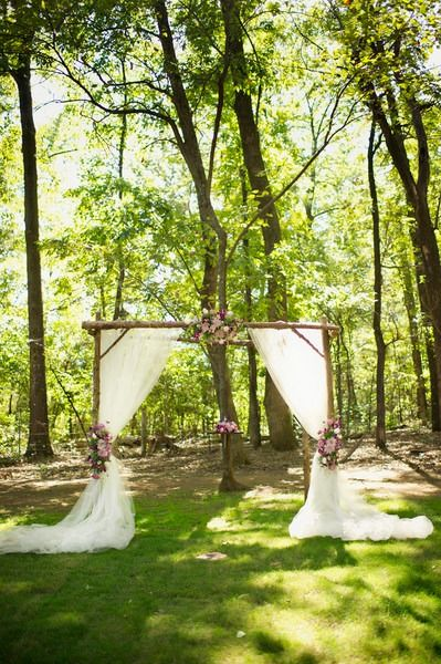 Simple wedding ceremony decor idea - outdoor wooden ceremony arch with draped white fabric and flowers {Melissa McCrotty}
