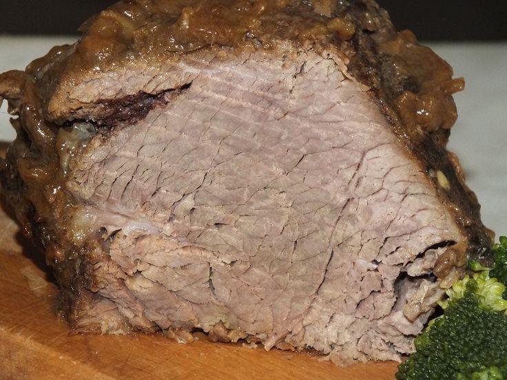 Przepis na pieczeń wołowa w sosie. Wołowinę opłukać i osuszyć. Cebulę obrać z łusek, opłukać i pokroić w piórka. Ułożyć na mięsie i polać olejem. Dodać listek laurowy, ziarenka czarnego pieprzu, ziarenka ziela angielskiego, szczyptę pieprzu cayenne, soli i czarnego pieprzu.