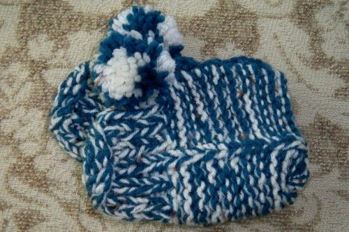 denim blue and white together make this pair of little slippers sturdy and warm. Knit with two strands of yarn throughout. They are accented with crocheted trim around the top and a blue and white pom