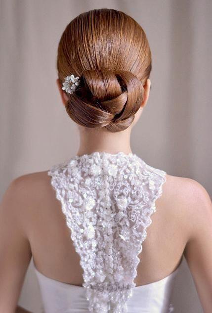 On commence cette sélection de 10 chignons par une coiffure très travaillée et originale. Le chignon est d'abord assez serré, pas un cheveu ne dépasse. Sur la nuque, les cheveux sont noués, plusieurs grosses mèches s'entrelacent pour former comme une fleur ou un gros nœud. C'est d'ailleurs une fleur qui est piquée dans bas du chignon, pour apporter une petite touche romantique à la coiffure. Sa couleur blanche rappelle d'ailleurs celle de la robe. Cette coupe convient plutôt à des cheveux…