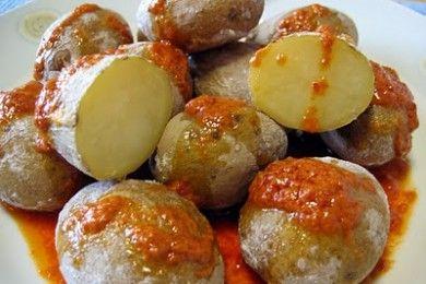 Las papas arrugadas son un plato muy típico de las islas canarias. Son patadas cocidas con piel en aqua salada, y se sirven con mojo picón, que es una salsa picante a base de aceite, ajo, guindilla y pimentón.