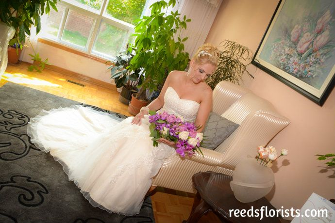 Taking a moment to admire her bouquet before the ceremony. Flowers by www.reedsflorists.com