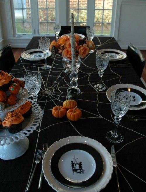 black cloth, white dishes and platters, silver, crystal, orange flowers & food