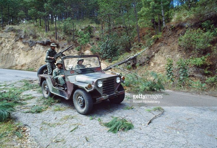 Guatemalan Army soldiers drive a jeep past a section of the Pan American Highway previously blocked by felled trees, during the ongoing civil war, Los Encuentros, Guatemala, March 1, 1982. They trees were downed by the Guerrilla Army of the Poor (EGP, associated with the anti-government Communist factions) to block the road the day of presidential elections. The war between state forces and Marxist rebels eventually lasted 36 years, before the signing of a peace treaty in 1996.