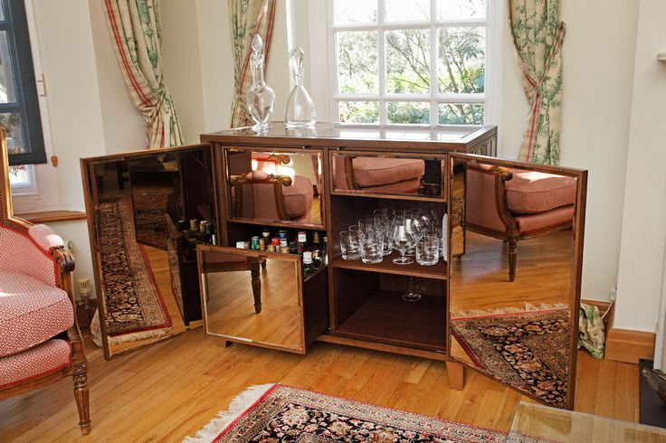 This drinks cabinet features 'antique' bevelled mirrors in narrow strips on the doors and sides. The interior is oak veneer which has been stained. by Andrew Manning Furniture