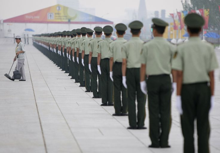 Chinese paramilitary soldiers line up by a sweeper near the National Aquatic Center while swimmers are in a practice session for the Beijing 2008 Olympics on August 6, 2008.    -photo by Itsuo Inouye / AP