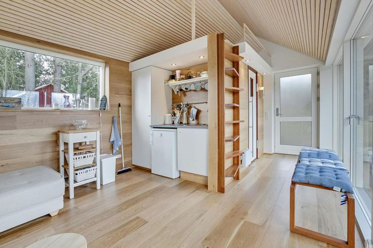 This tiny home features a large, glazed wall and a comfortable interior with all the amenities.