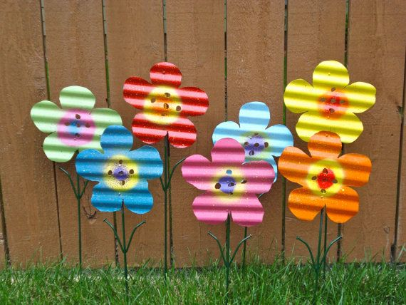 "Metal flowers made from corrugated roofing tin, 1/4"" stakes and roofing nails for leaves"