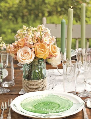 I love the flower arrangement in the mason jar with twine. And the accenting green candles with the orangish pink flowers
