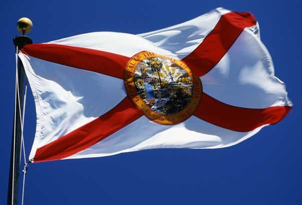 Florida State Flag - On a white field emblazoned with a red X and the state seal, Florida's flag represents the land of sunshine, flowers, palm trees, rivers and lakes. The seal featrues a brilliant sun, a cabbage palmetto tree, a steamboat sailling and a Native American Seminol woman scattering flowers.