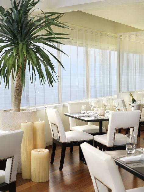 As in the design for the rest of the hotel, Thomas wanted to bring a beach vibe to the Penthouse Restaurant, even though it is up on the 18th floor.  White upholstery and sheer white curtains reflect the sun and sand atmosphere while specific touches like dolphin-shaped chair backs and a seashell-imprinted bar reference the sea. The plank hardwood floors give the feeling of a boardwalk while curtained cabanas serve as banquettes, though each has a Murano white chandelier for a touch of…