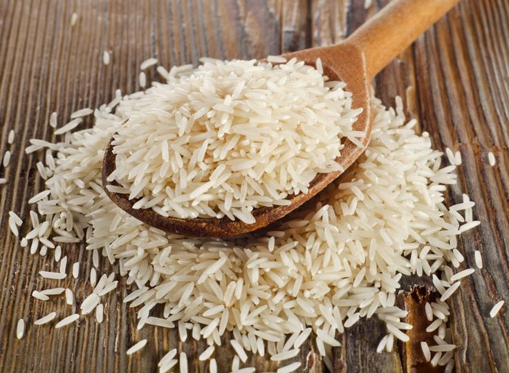 Raw basmati rice in  wooden  spoon . Selective focus