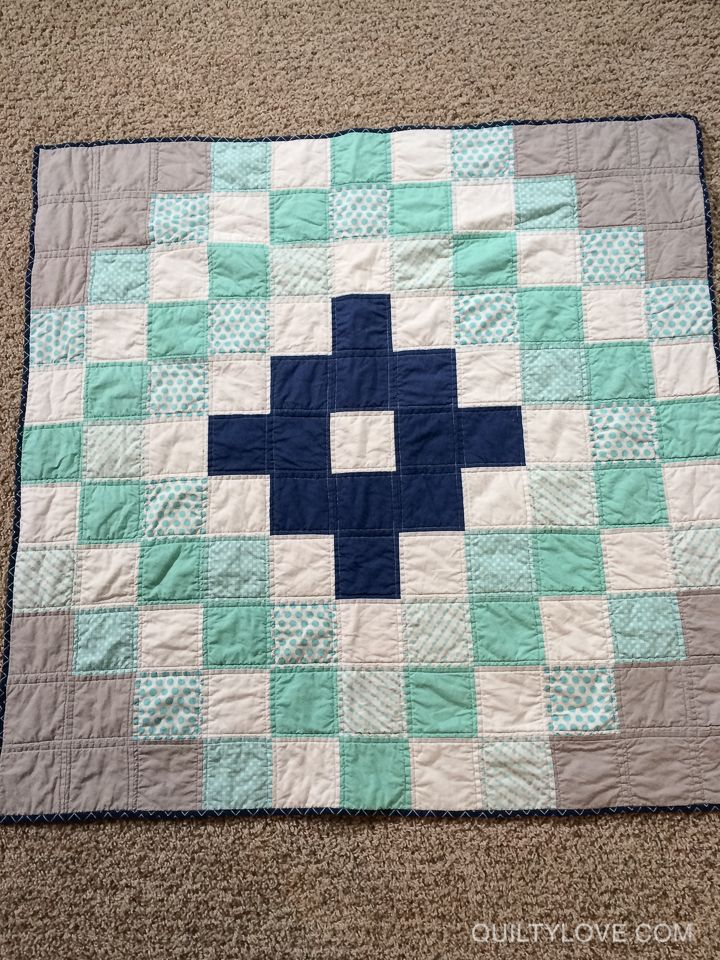 "This baby medallion quilt is super easyand uses charm packs.   Charms are 5"" square.This quilt uses an assortment of turquoise scrapsI had on hand along with a bella solid navy charm pack.I just layed out the pattern I wanted to make and sewedit together in rows."