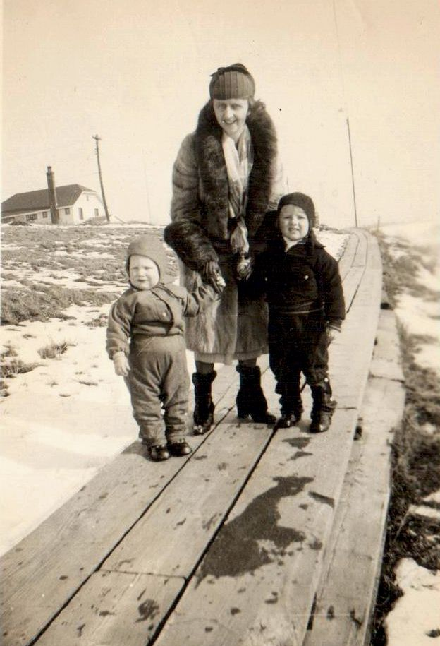 John, Don, and Claire Romkey on the boardwalk to the refinery 1930s. Superintendent's home on Avenue B is in the background