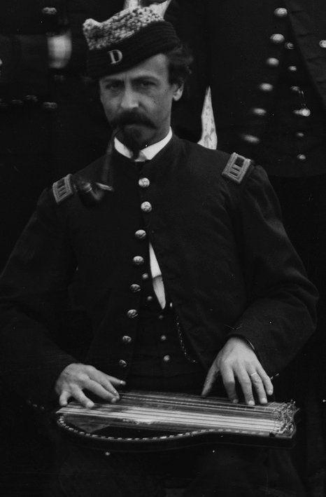 """Captain John J. Eberhardt The soldier playing the zither is captain of Company D, as signified by the rank on his shoulder boards and the prominent """"D"""" on his cap."""