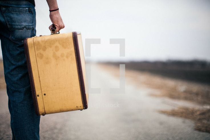 close-up of a man carrying a suitcase looking down a long road // second chances are ahead