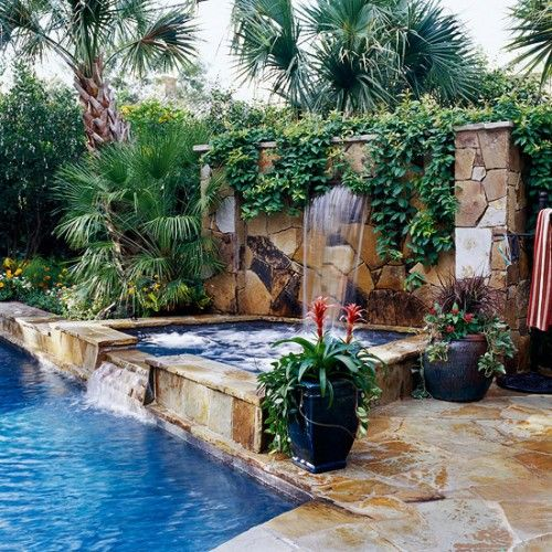 Hot tub with a waterfall. The stone wall with all of the trees and plants reminds me of the Jungle Book!