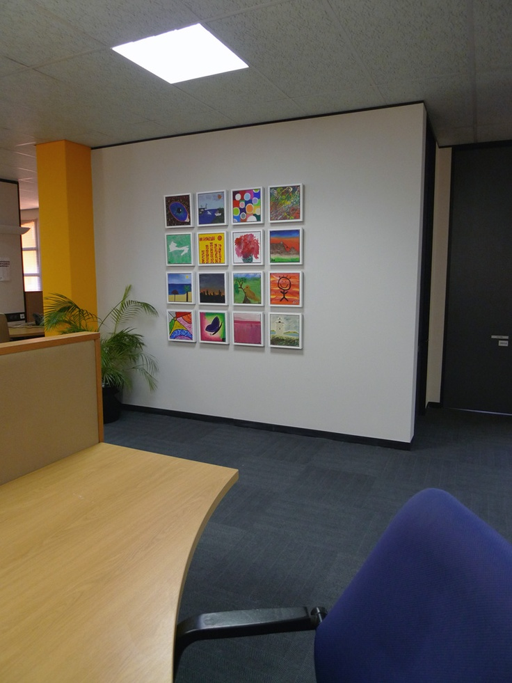 Team art jamming canvases framed and displayed as an art wall