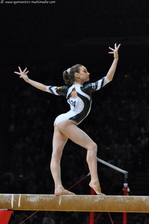 gymnast performing on balance beam, gymnastics
