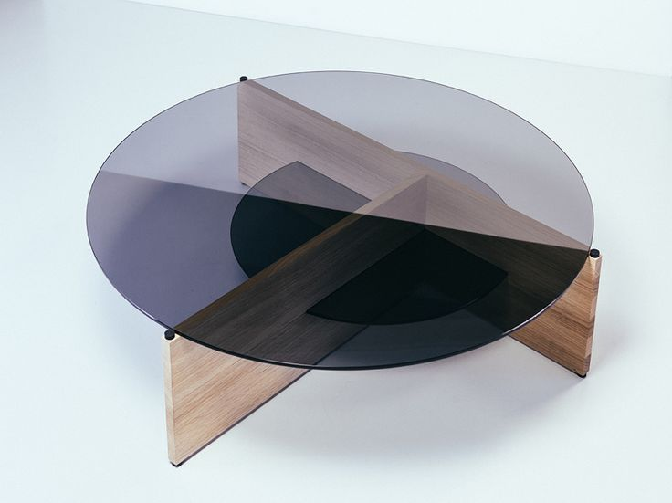The Divide coffee table is a collapsible composition of flat surfaces. It is easily transported as a flat-pack and efficiently manufacturable. The smaller glass circle works as a vitrine shelf and a patch that binds the structure of this simple three-dimensional puzzle. Matt oak and grayscaling layers of shiny smoked glass form an intensive contrast celebrating the beauty of basic forms and natural materials. Design: Elina Ulvio