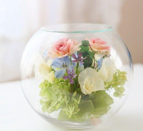 『季節の花たちをシリカゲルで乾燥加工して綺麗な色のままガラス容器内に一つ一つ丁寧に手作りで仕上げさせて頂きます。 ガラスの容器(ボトル)を密封することで5~15年以上(環境によっても変わります)そのままの美しいお色を保つ事ができます。 長くお色を保つために直射日光の当たらない場所に置いて下さい。 いつまでも変わらない・ほこりの心配もく拭くだけのボトルフラワーはお祝いの贈り物ギフト、プレゼント、仏花としても皆様に大変喜ばれています。 プリザーブドフラワーより長持ち!でナチュラルで自然なお色のお花です。 これからの季節、母の日のプレゼントにいかがでしょうか』※受注制作でお受けしていますので発送は1週間以内で発送させて頂きます。お急ぎの方はご連絡下さい。※ハンドメイド制作ですので若干花のお色、形が変わる事もありますのでご了承下さい。■Lサイズのボールボトルにバラとスイトピー、アジサイをアレンジしました。…